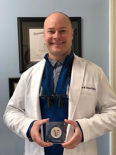 Reno Dentist Dr. Jason Alford holding a Veteran Coin from Google