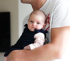 photo de bébé dans les bras de son papa