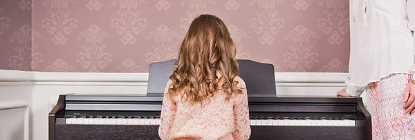 Child sitting at a Roland digital piano