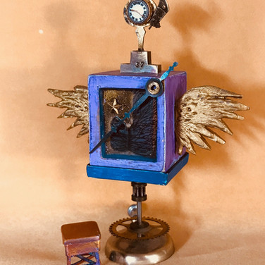 Timekeeper  From Flying Box series of 150 tiny boxes with drawers and wings all symbolizing themes.  Mixed media, wood, metal clay.