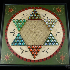 Chinese checkers set with  60 marbles on a signed wood game board.
