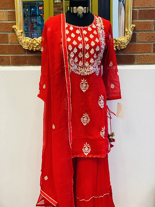Red color short kurta with pittal work on neckline comes with sharara