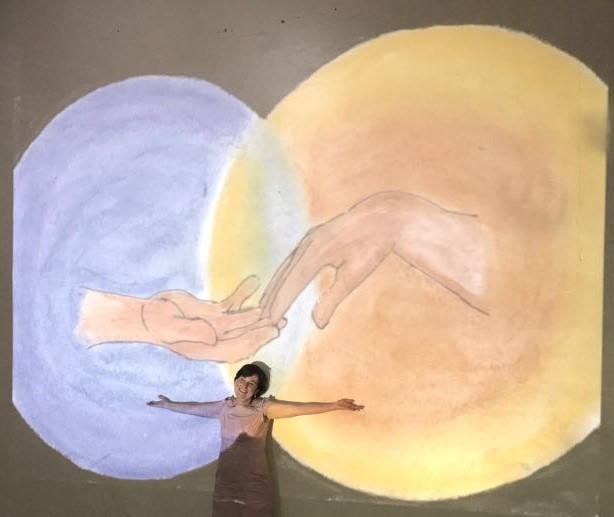 Ao fundo, em uma projeção, duas mãos se tocando, cada uma saindo de um círculo. E eu de braços abertos na frente da projeção.
