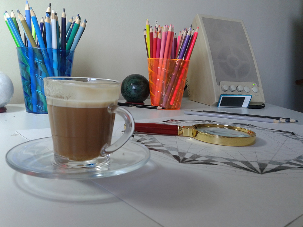 em uma mesa, dois copos com lápis de cor e uma caixa de som ao fundo, uma lupa em cima de um desenho inacabado de uma mandala e em primeiro plano, uma xícara de café.