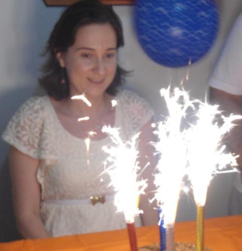 Uma moça sentada à mesa contando parabéns com quatro velas acesas.