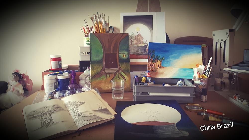 Mesa de pintura de Chris Brazil com alguns desenhos e pinturas de árvores, casa, e praia, bem como tintas e pincéis.