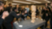 Jenga game with an NYU CAC adviser pulling a piece while the crowd cheers.