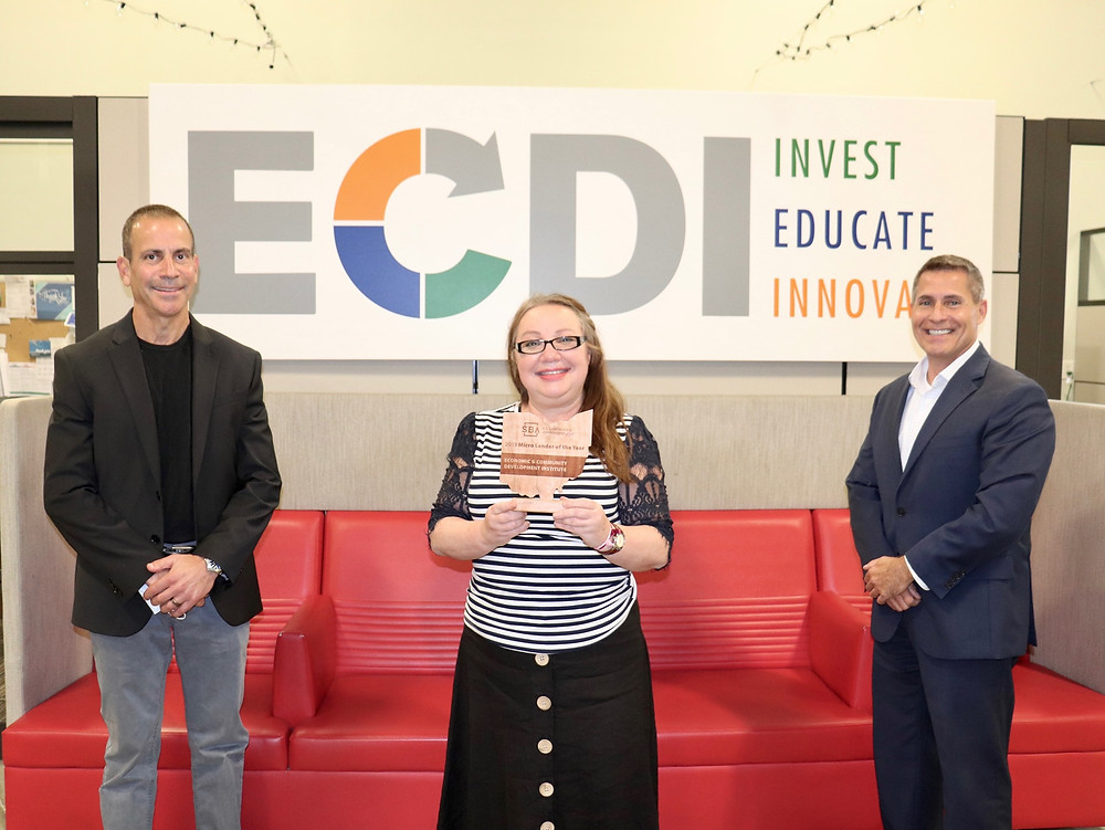 CEO and Founder of ECDI, Inna Kinney, poses with the SBA award presented to her and ECDI President, Steve Fireman, by SBA Regional Director, Everett Woodell