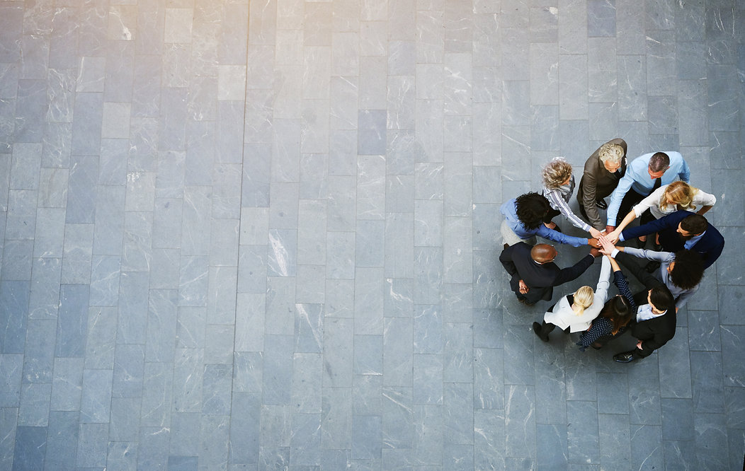 High angle view of a team of united businesspeople standing with their hands together in a