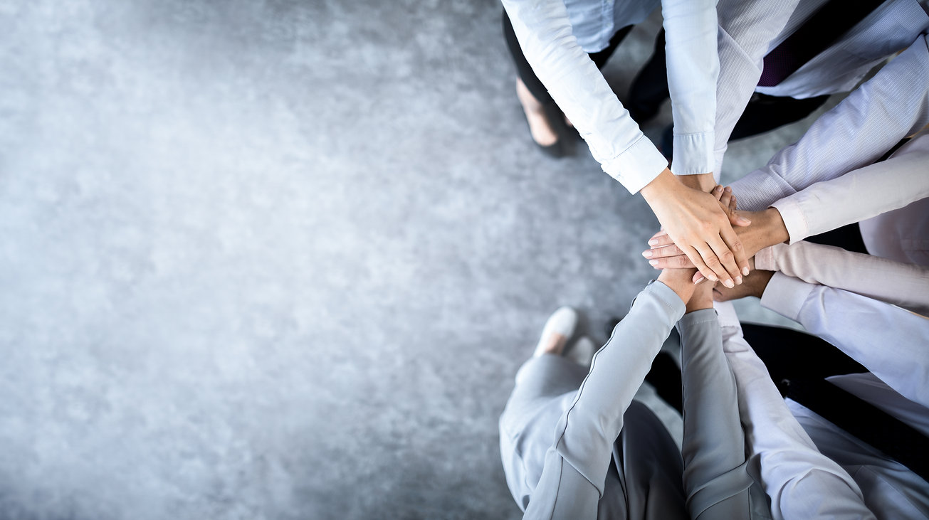 Close up top view of young business people putting their hands together. Stack of hands. U