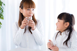 Mother and daughter drinking water