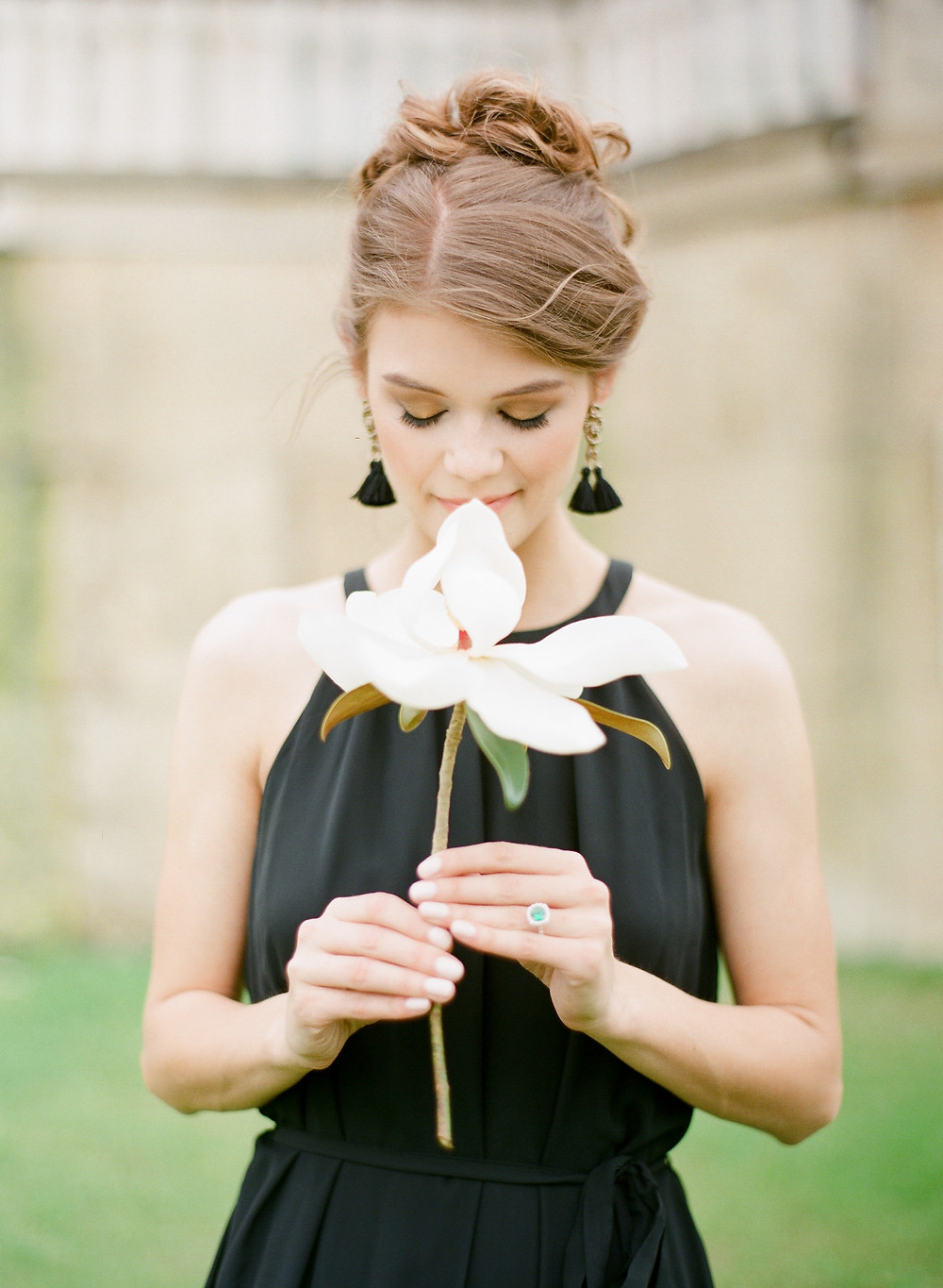 Woman looking down holding a single magnolia flower wearing emerald engagement ring