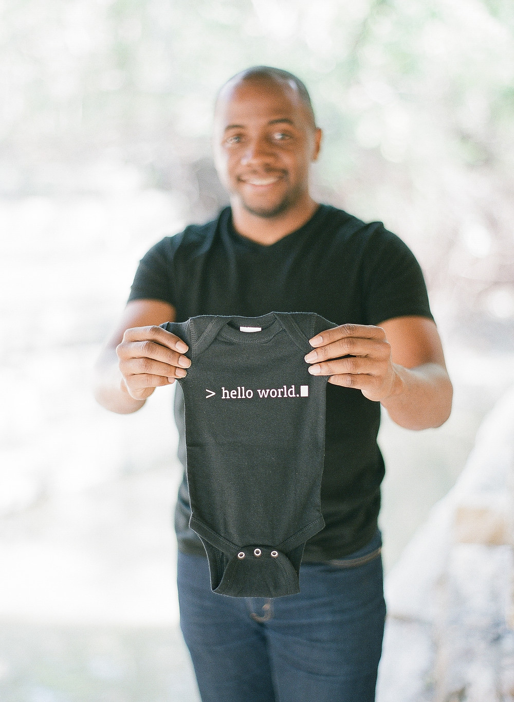 Father to be holding baby onesie hello world