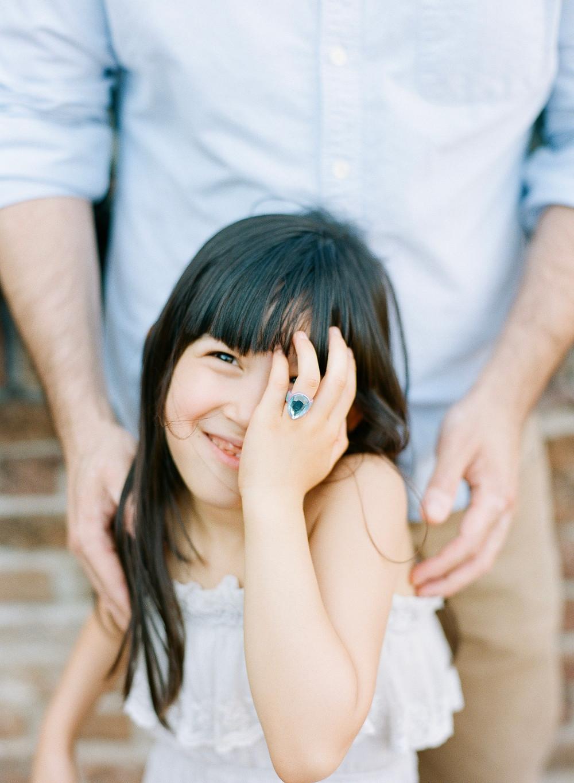 Interraccial girl looking at camera smiling during family portraits at Castello di Amorosa