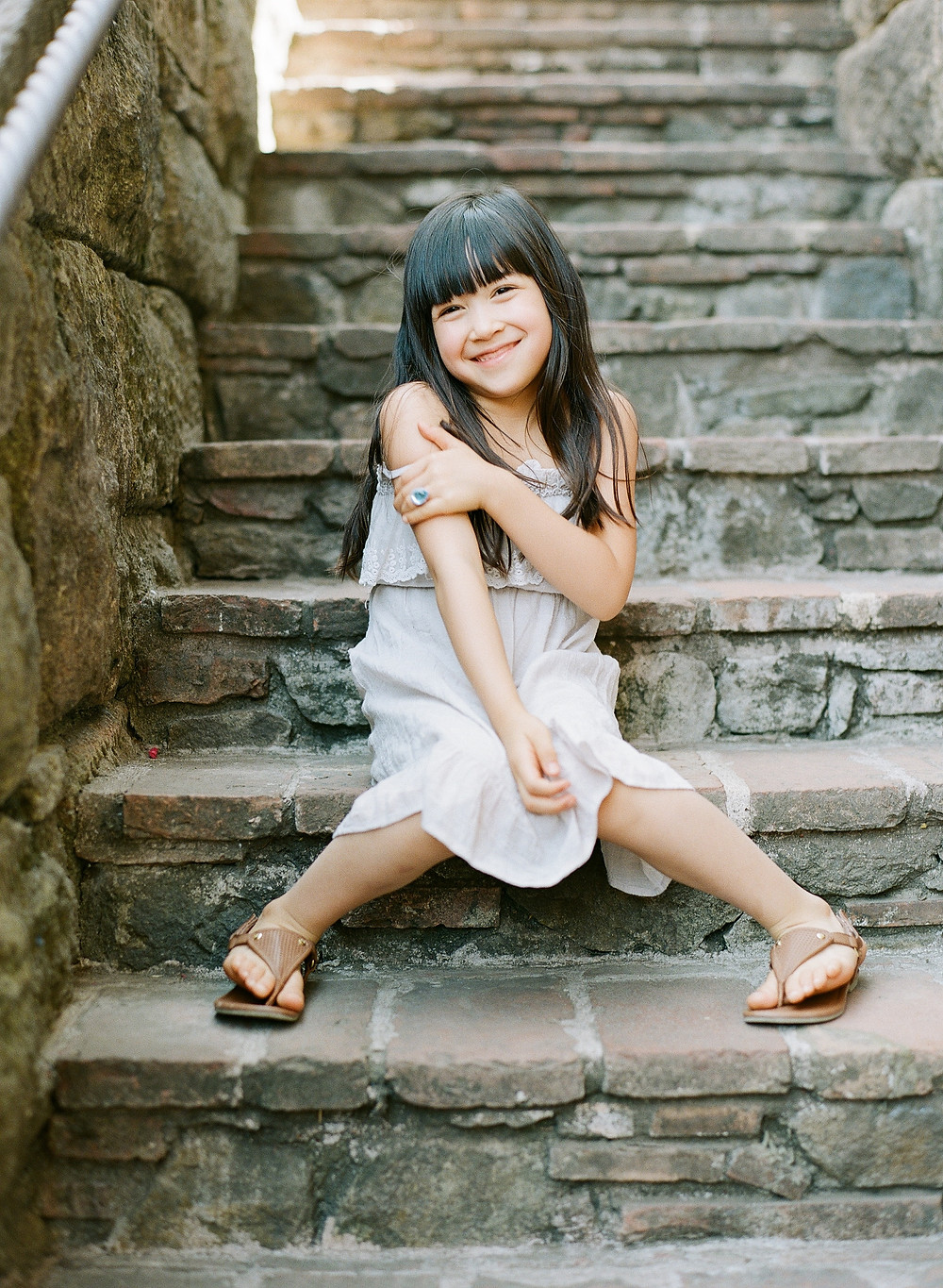 Little girl looking at camera wearing a while dress and sandals during family portraits