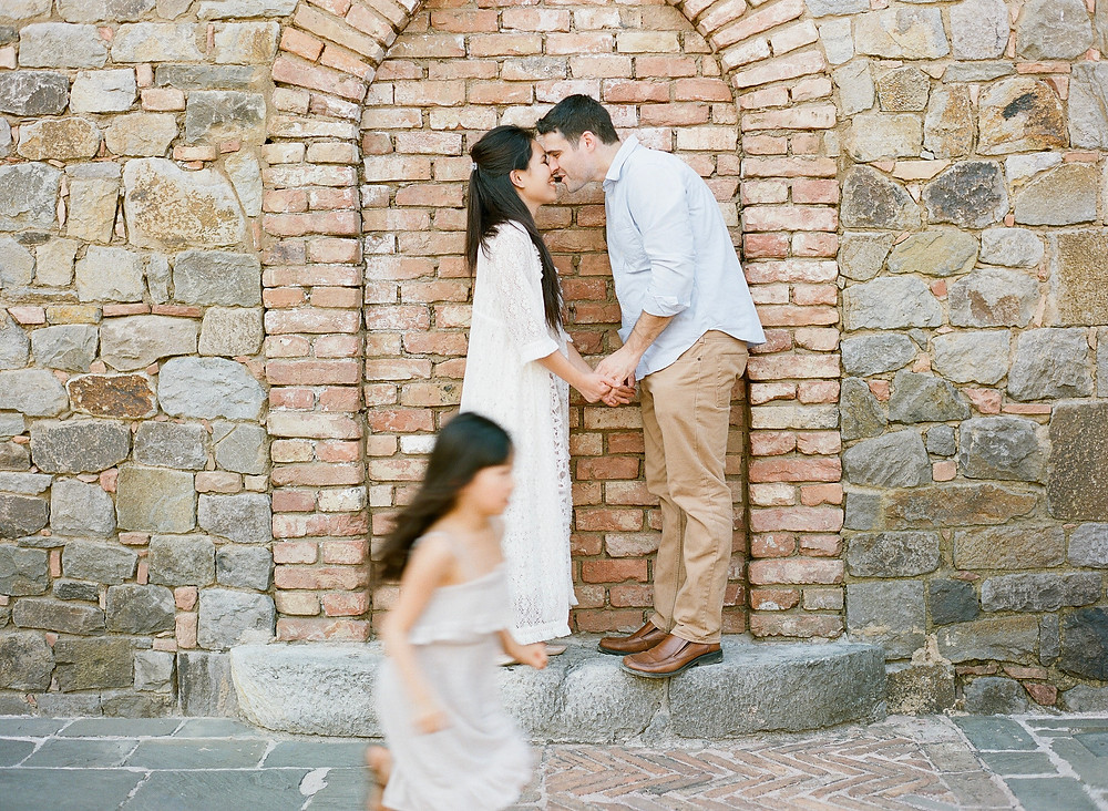 Mom and ad kissing while daughter runs during family portraits at Castello di Amorosa