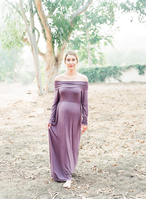 Woman wearing purple maternity photos walking