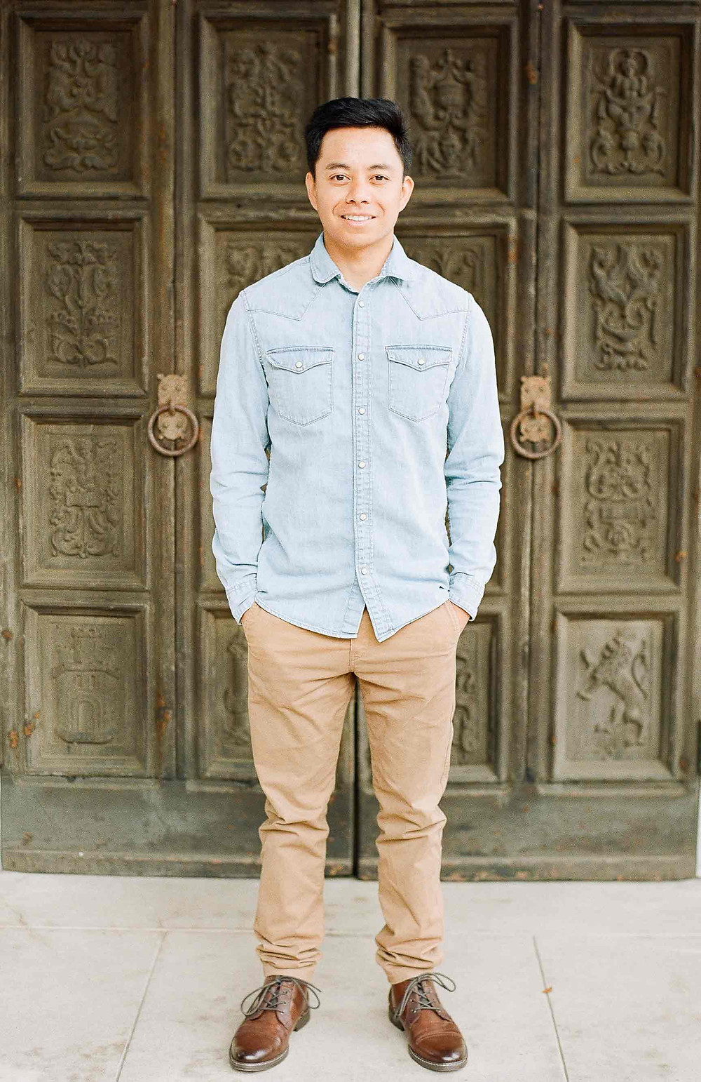 Asian Man in blue shirt looking at camera with hands in pocket
