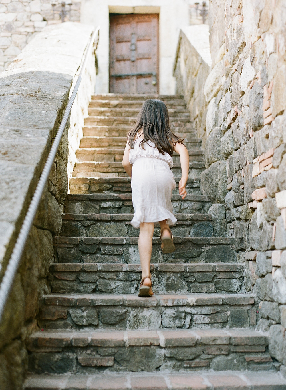Little girl running up stone steps during family portraits on film at Castello di Amorosa