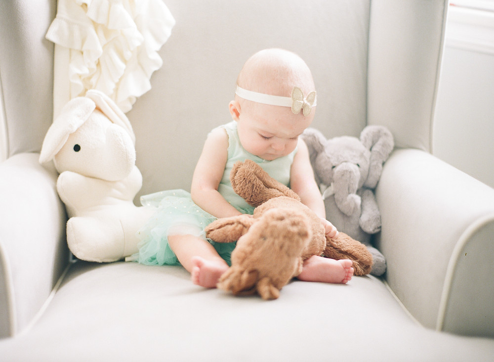Photo of toddler wearing teal tutu playing with stuffed animals at home in Burbank
