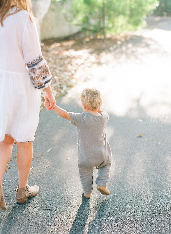 Mom holding toddler hand walking in Palos Verdes