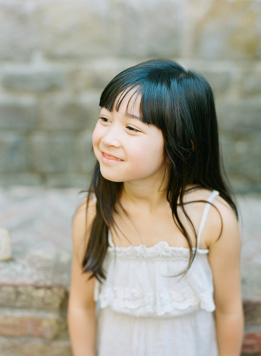 Little girl with black hair looking away smiling wearing a while dress at Castello di Amorosa