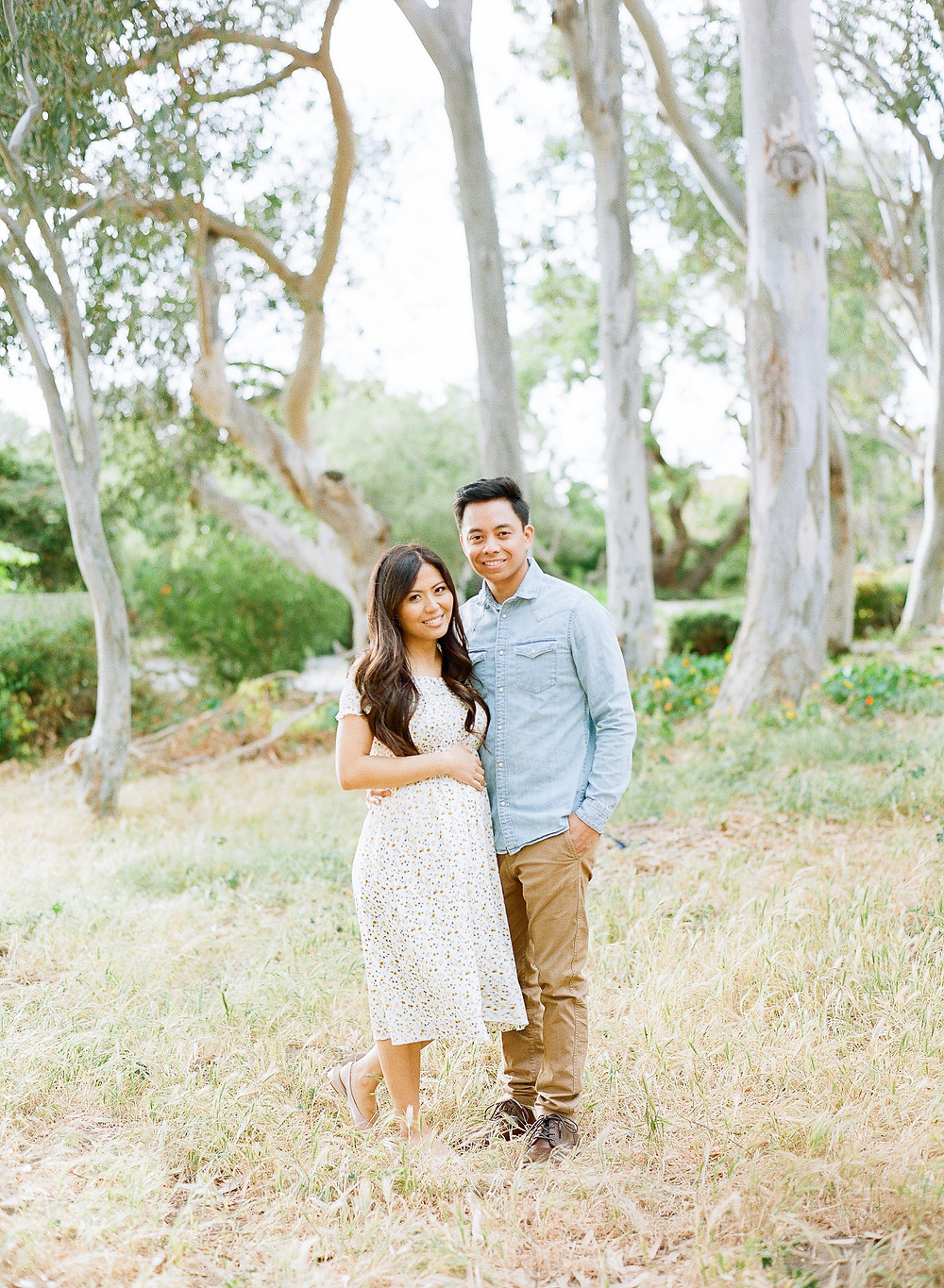 Pregnancy Announcement asian couple smiling looking at camera