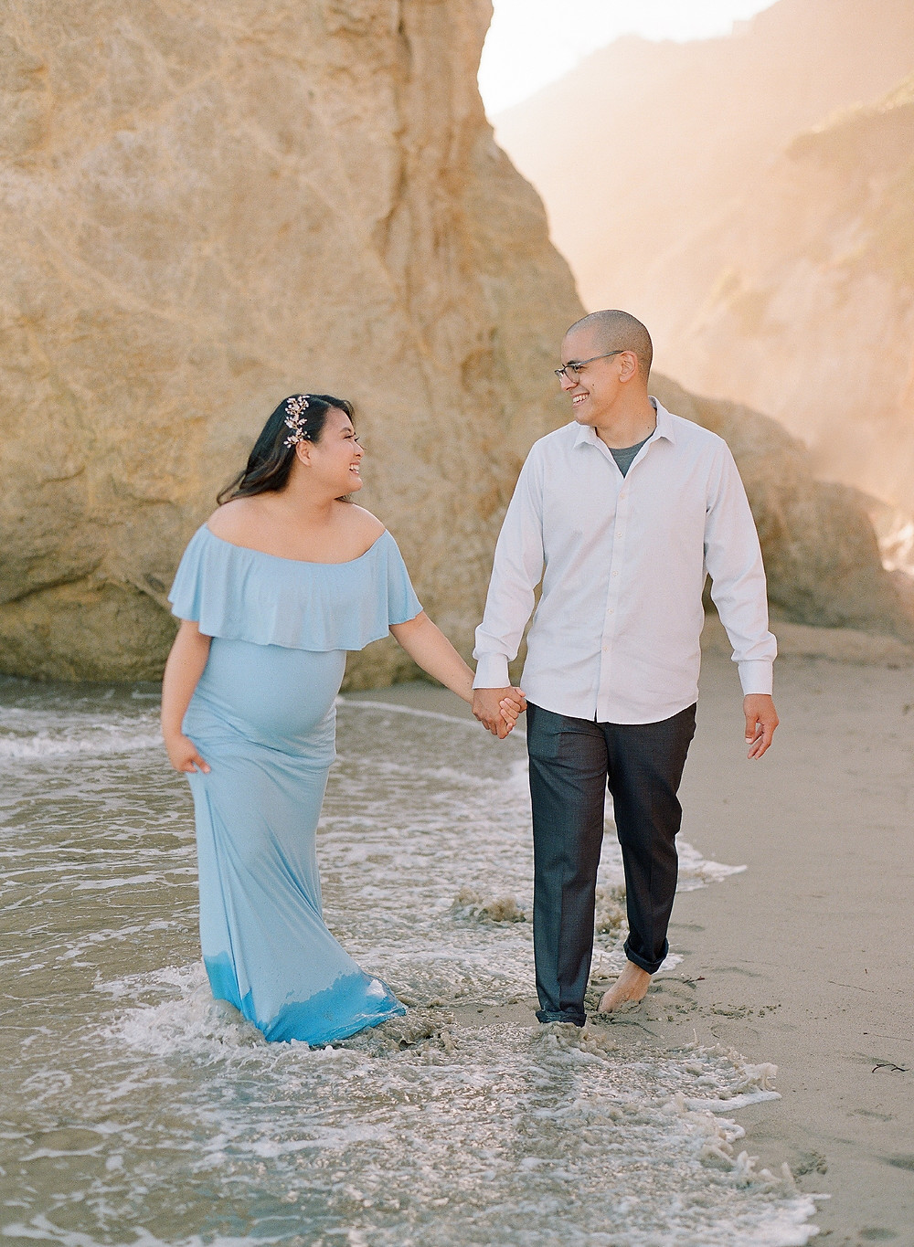 Maternity portraits of mom and dad walking on the beach laughing and looking at each other
