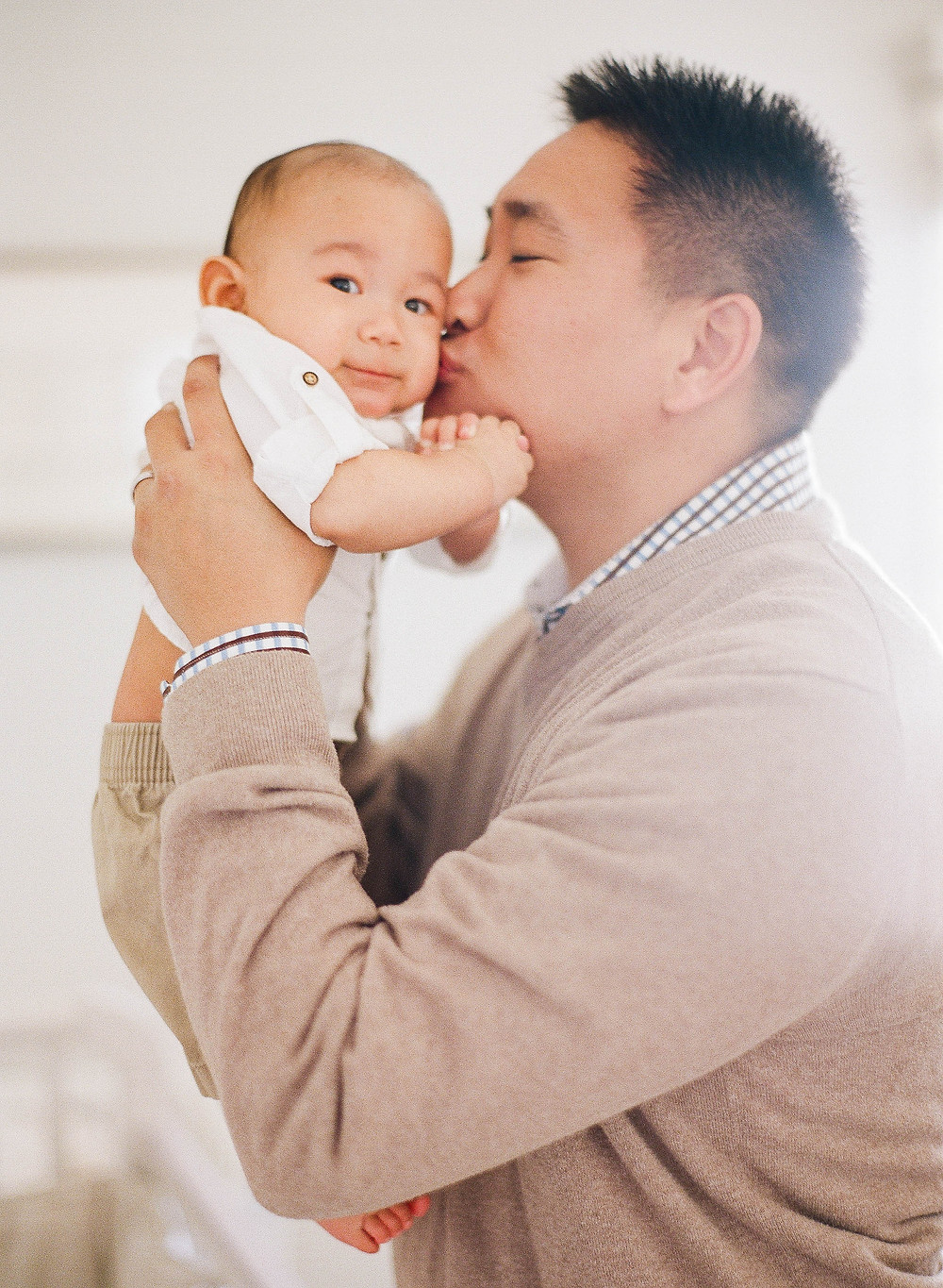 At home family portrait on film in los angeles with asian dad kissing baby's cheek