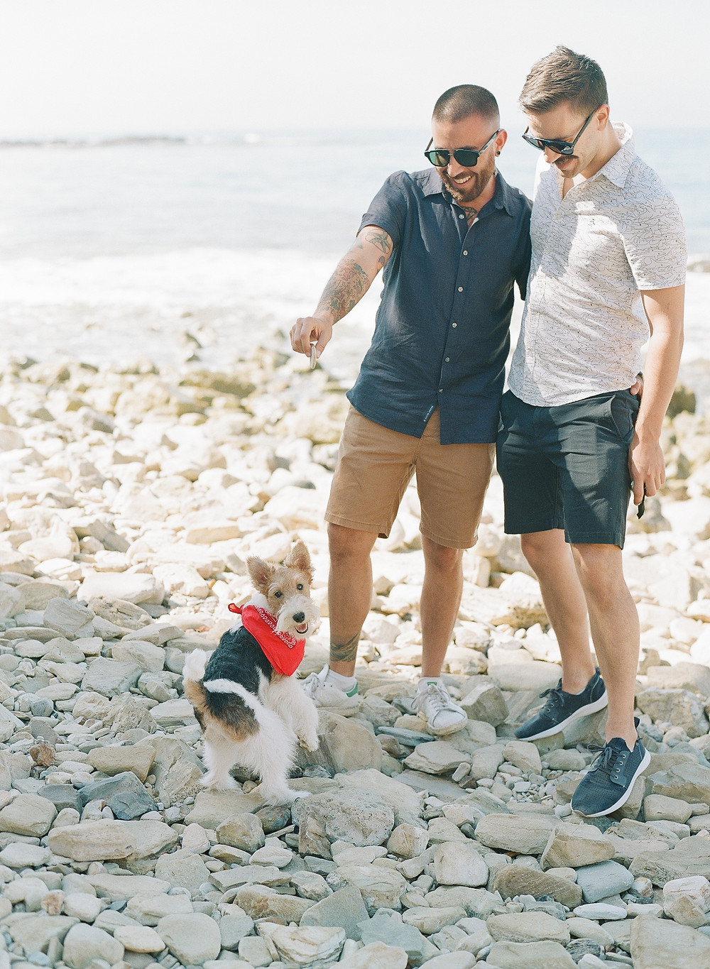 Gay couple playing with dog during family portraits on film at Palos Verdes