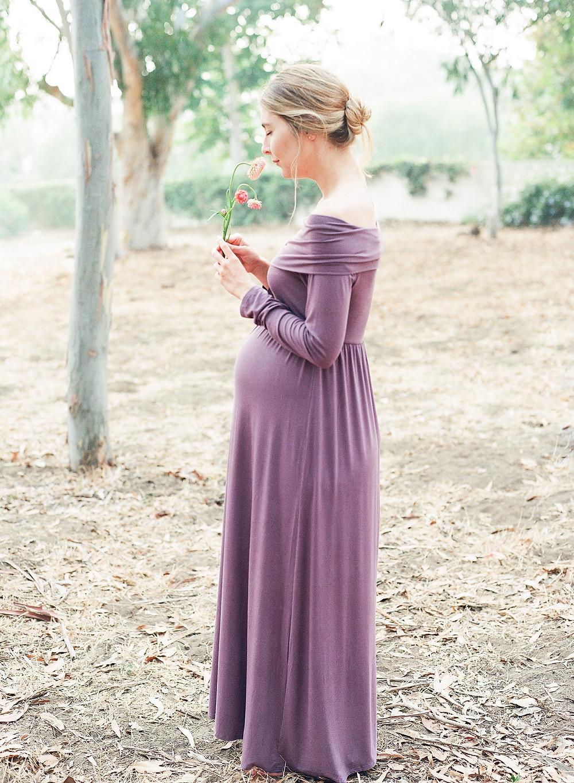 Maternity shoot in palos verdes woman wearing purple dress smelling a flower