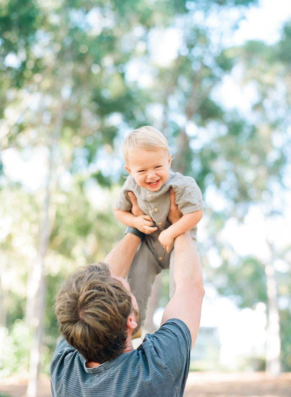 Toddler held up in the air by dad laughing at Palos Verdes Family Portraits