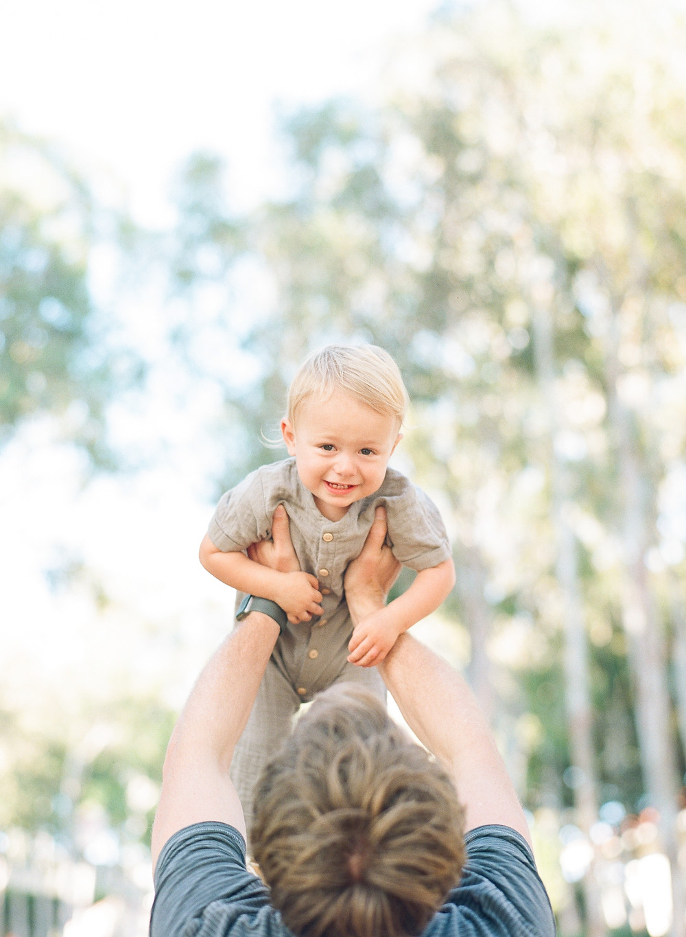Blonde toddler held up in the air by dad Palos Verdes family portraits
