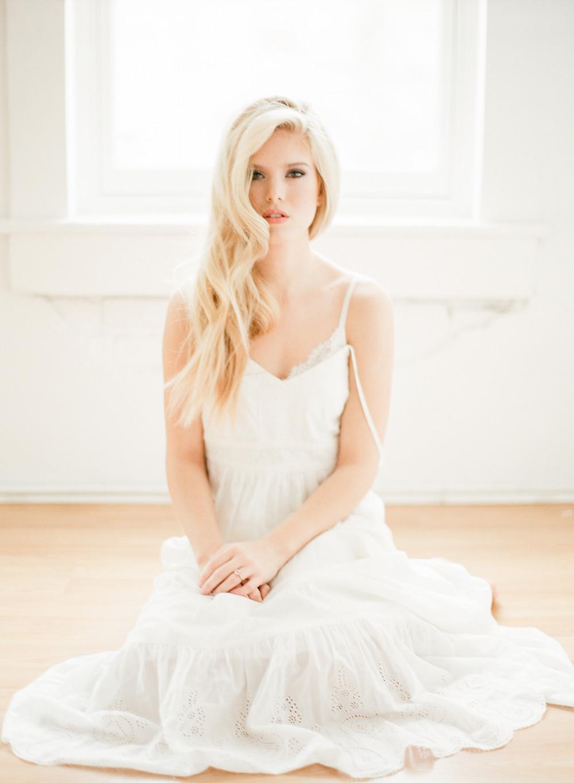 Boudoir photos of woman wearing a white lace dress