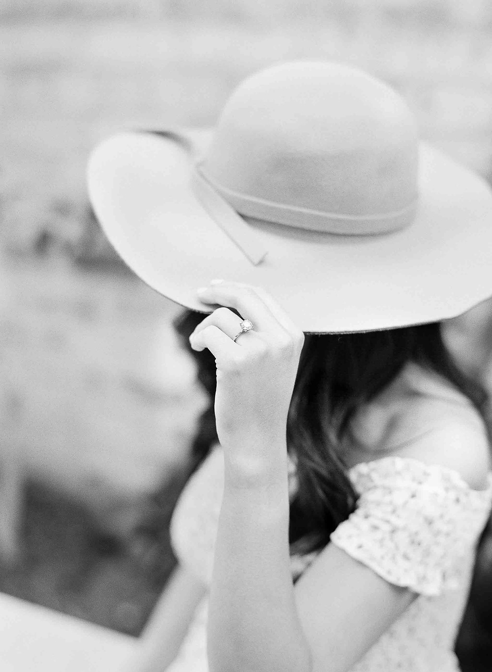 Woman touching brim of hat with diamond engagement ring