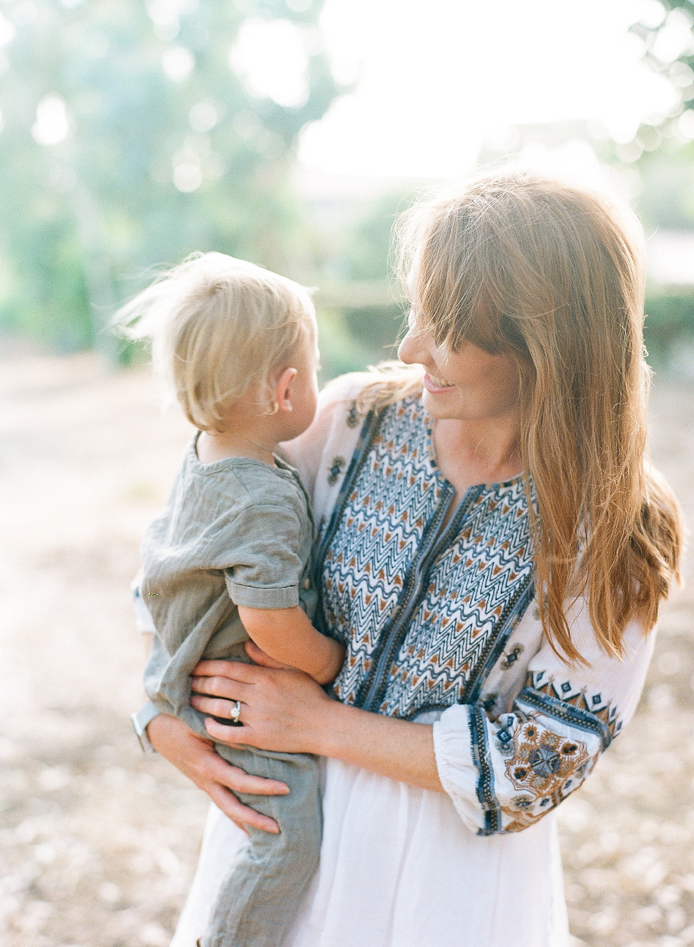 Mom looking lovingly at blonde toddler family portraits