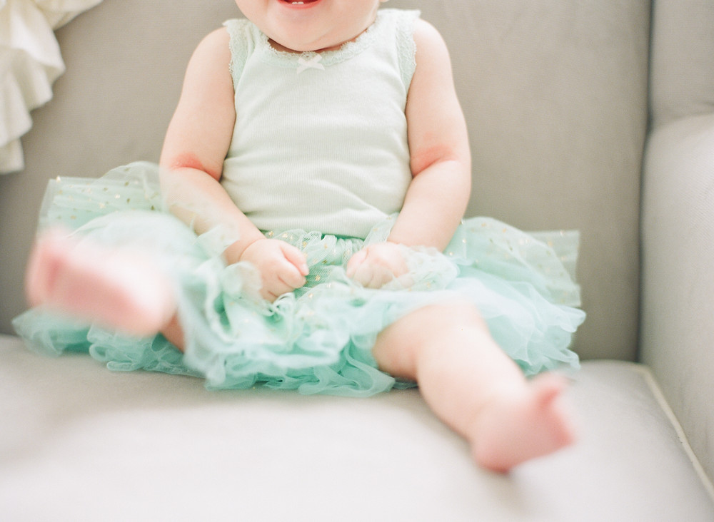 Close up of toddler wearing teal tutu and tank top at home