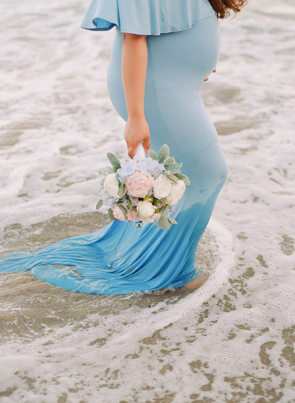 Maternity portraits of mom in Malibu wearing blue dress in the water