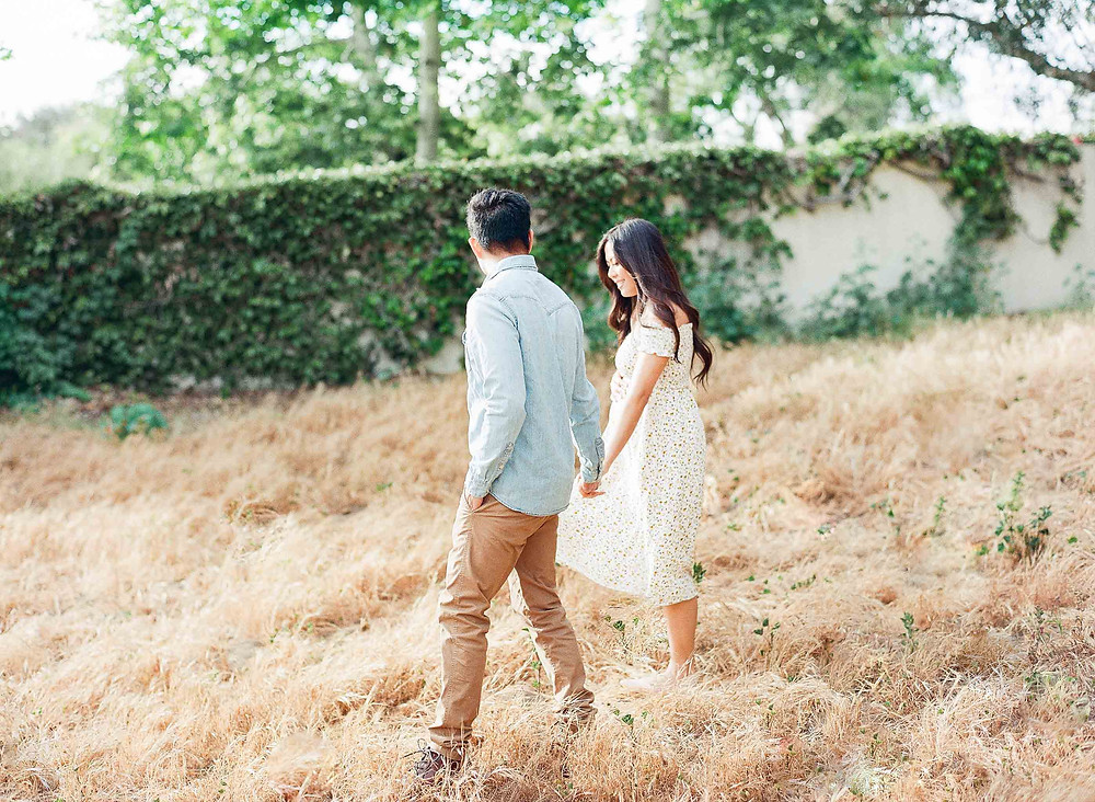 Man guiding pregnant wife in dry grass Palos Verdes