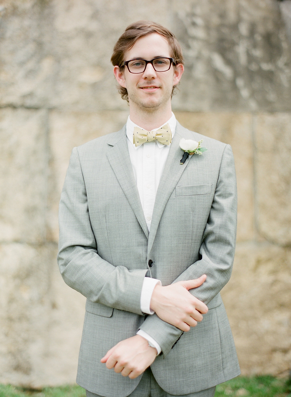 Man wearing brooks brothers bow tie and eye glasses during engagement photos in Mckinney Texas