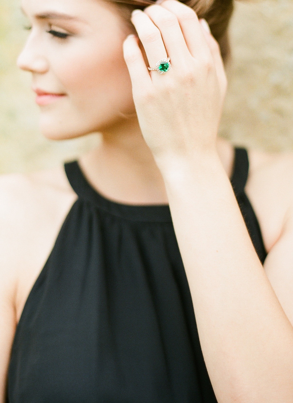Large Emerald and diamond engagement ring on fingers in McKinney Texas