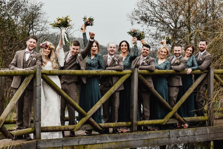 Wedding Photographer Birmingham, fun wedding photograph of the bridal party standing on a bridge at Wootton Park in Warwickshire