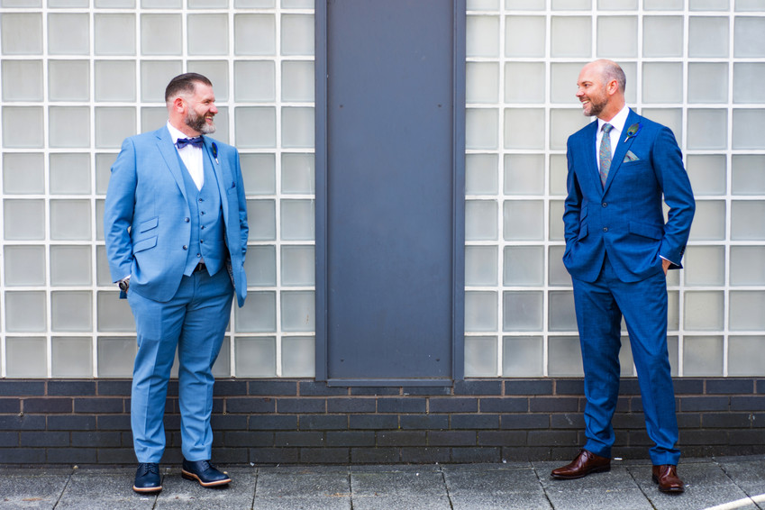 Same sex wedding photographer Birmingham, the two grooms looking at each other, full length shot outside Birmingham register office