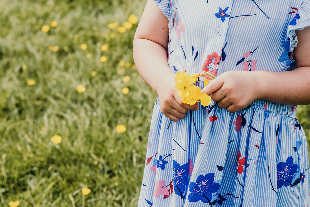 family Photographer Solihull, arty photograph of a young girls hands holding buttercups