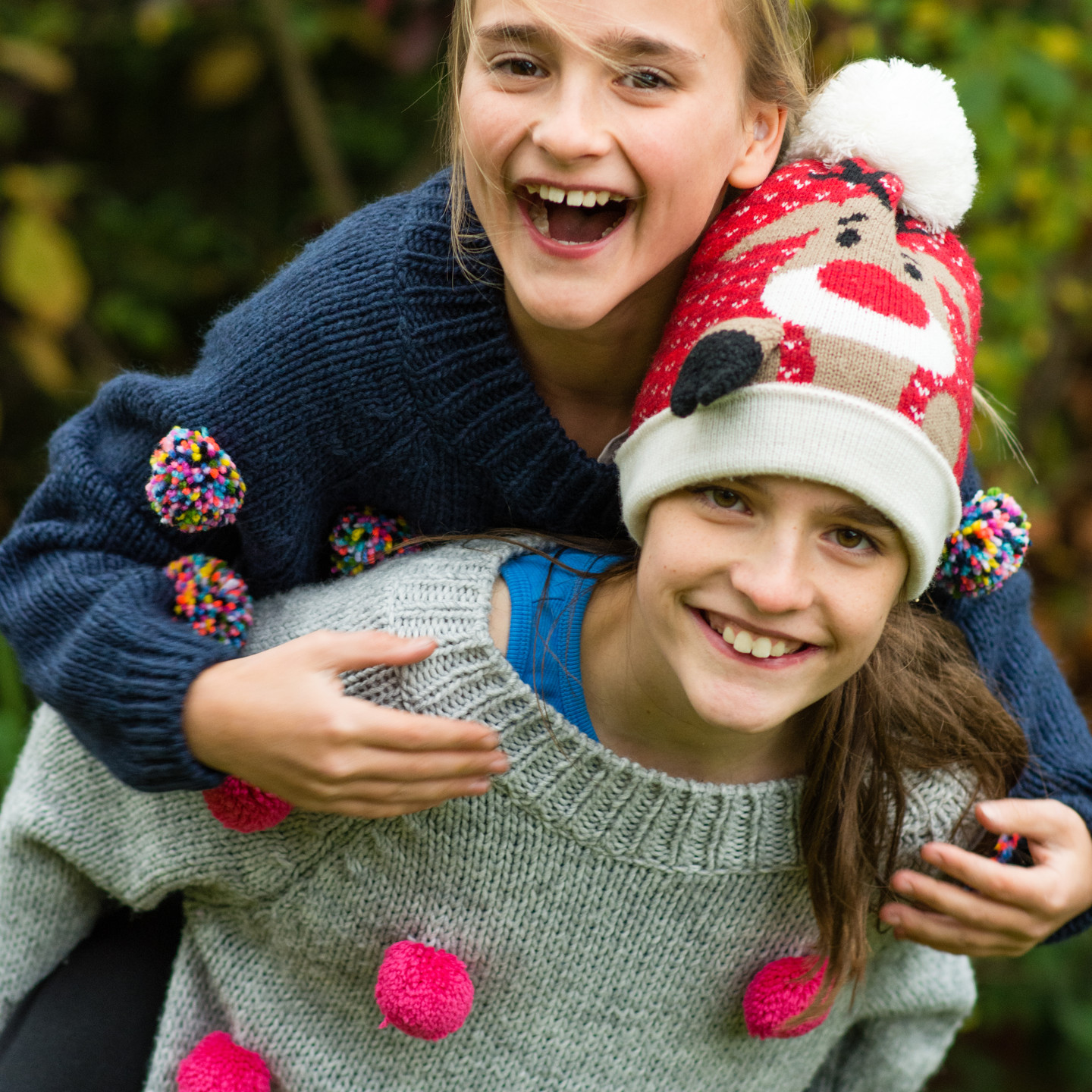 Family photography shoot outdoors, young girls giving each other a piggyback, natural photo shoot
