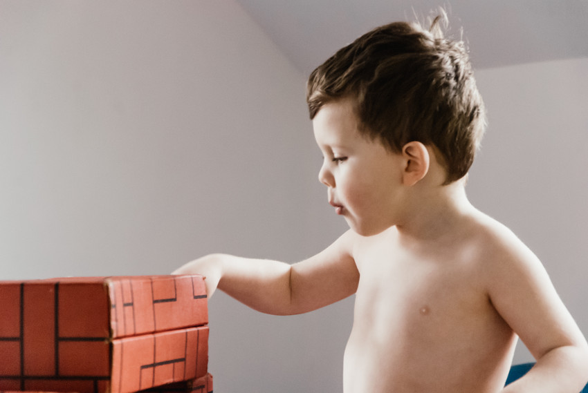 Lifestyle photo shoot for a little boy with autism, little boy playing with his toy bricks