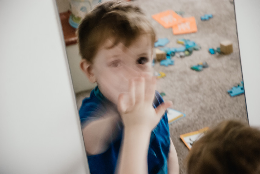 Lifestyle Photographer Solihull, photographing children with autism in their home in a natural way, little boy looking in the  mirror blurry image for effect