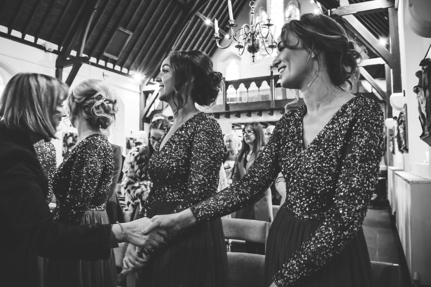 Wedding Photographer Birmingham, the bridesmaids shaking hands with the guests during a catholic wedding ceremony