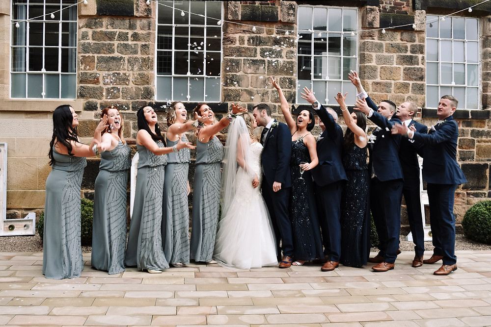 Wedding Photographer Solihull, Birmingham, the bridal party throwing confetti white the bride & groom kiss at The West Mill Derby
