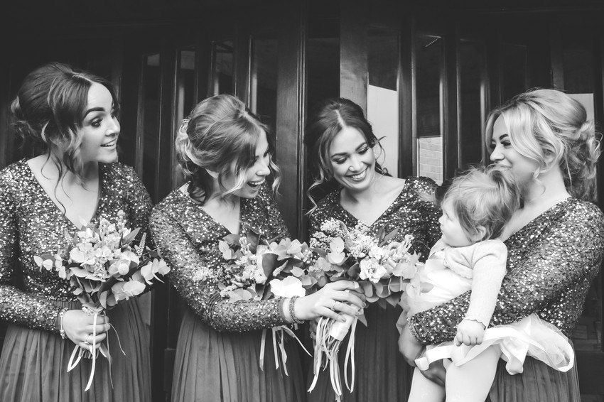 Solihull wedding Photographer, the bridesmaids & the flower girl, natural image looking at each other smiling